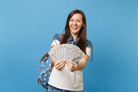 Portrait of female college student laughing in denim clothes with backpack holding bundle lots of dollars