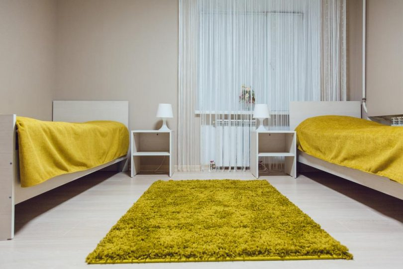 Dorm room layout with white walls, white floors and green carpet and bedding