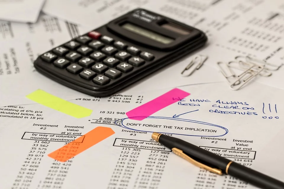 Accountants desk with calculator, pen and reports