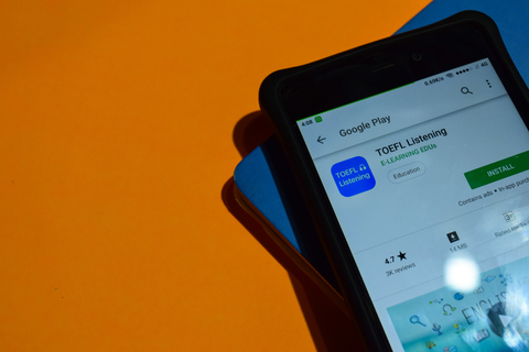 TOEFL app on smart phone screen sitting on orange background