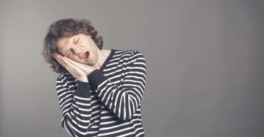 Male college student in striped black and white sweater wants to sleep. Put his head in his hands and closed eyes while yawning. Standing on the grey background.