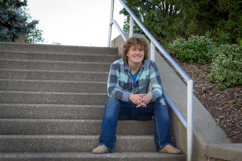 curly haired male college student smiling and sitting on steps outside
