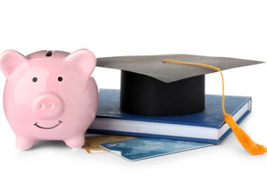 Graduation hat, credit cards and piggy bank isolated on white