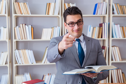 Male college law student with magnifying glass reading a book