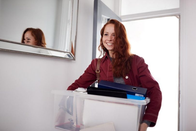 Female college freshman holding box moving into dorm room