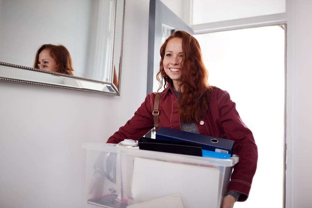 Female college freshman holding box moving into dorm room