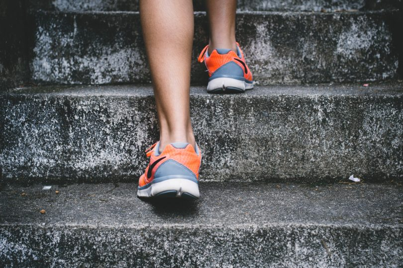 back of runners feet and legs running up stairs with running shoes on
