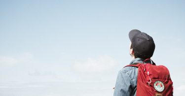 College student wearing hat and backpack looking up into the sky