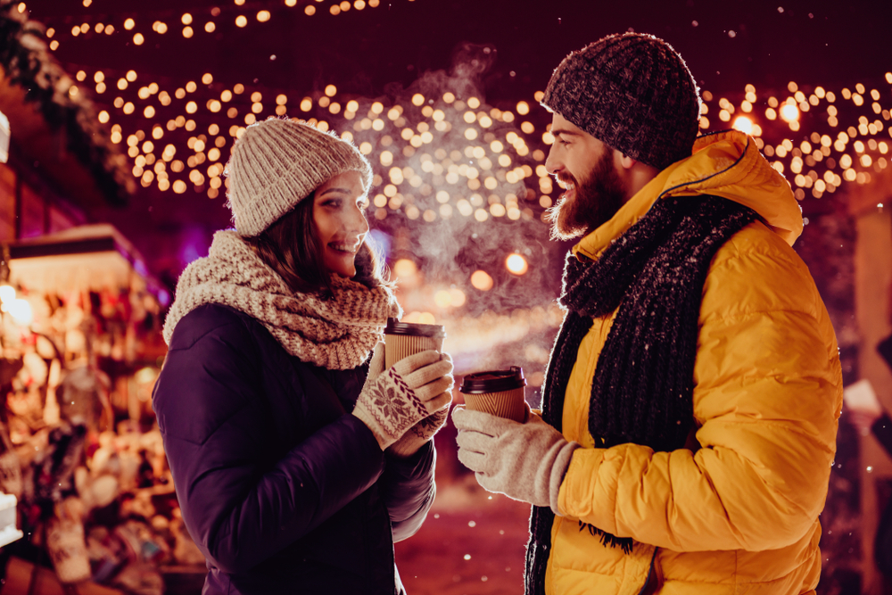 couple on date outside in the winter holding hot drinks