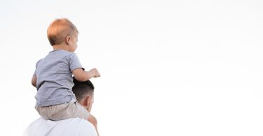 dad holding son on shoulders looking at the sky