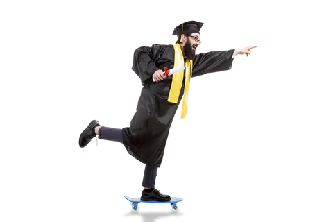 bearded male graduate riding a skateboard, pointing forward and holding diploma on white background