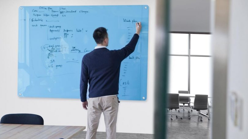 College student writing on glass magnetic white board