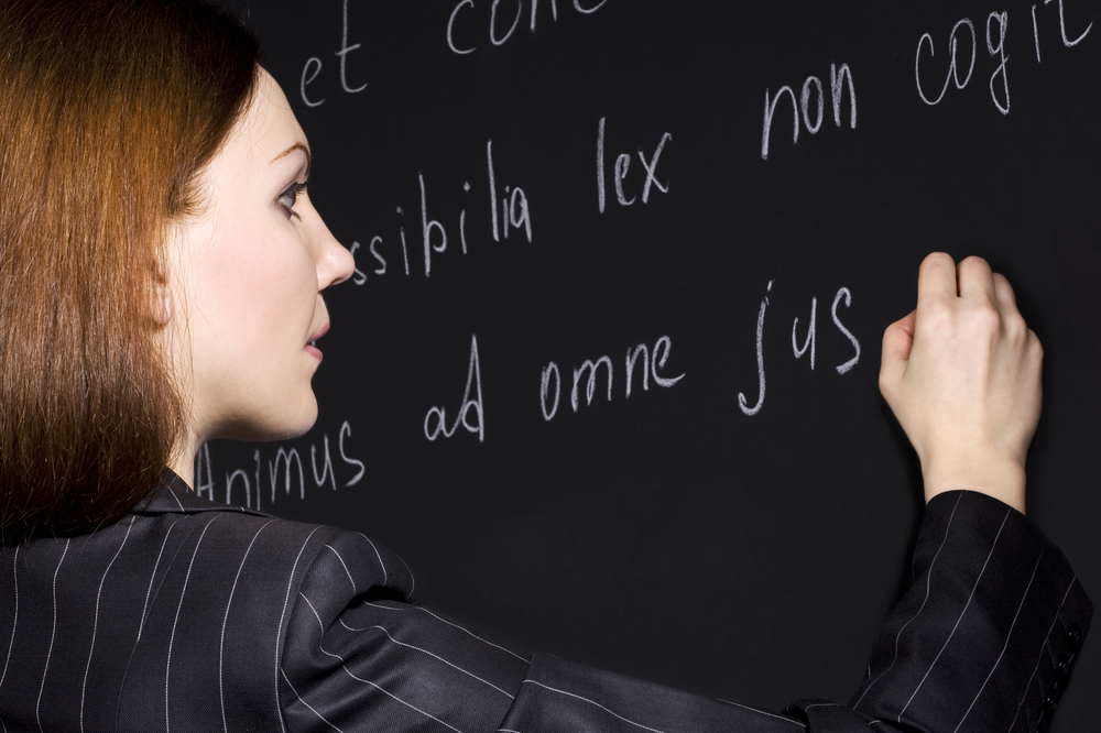 female teacher writing in Latin on chalk board.