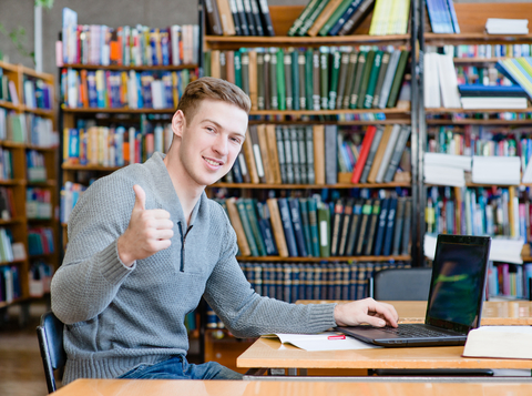 Student with laptop showing thumbs up in the university library