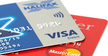 mastercard and visa credit cards sitting on white background