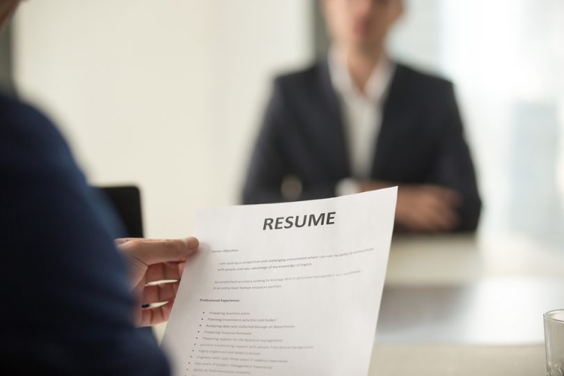 employer holding up resume at desk, interviewee sitting in the background