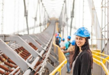 smiling female in blue hard hat working on site