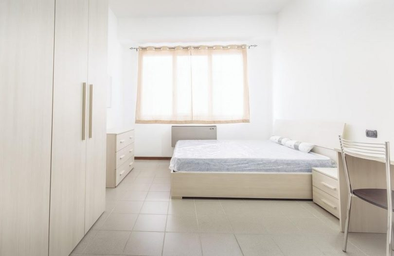 Empty white dorm room with a window