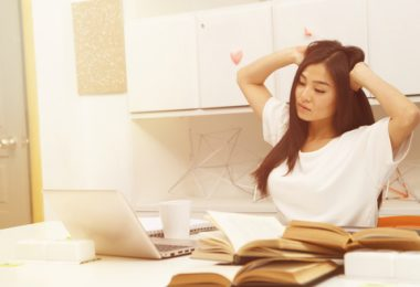 exhausted Asian student sitting in front of laptop computer