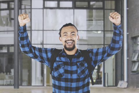 male college student raising hands while celebrating his success