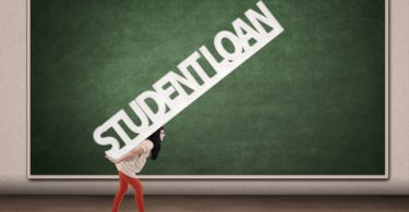 female college student carrying the giant words Student Loan on her back in front of a chalk board