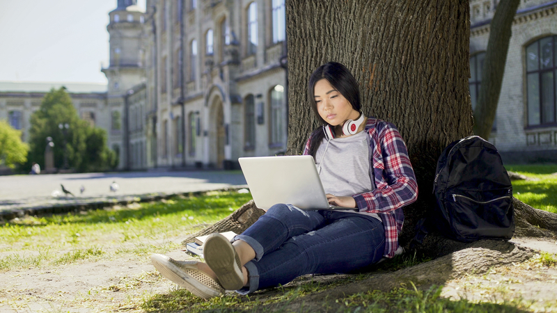 College student sitting under tree in campus, using laptop doing online course