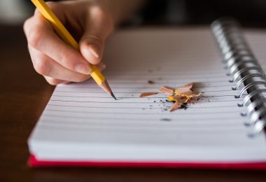 college students hand writing with a pencil on notebook with pencil shavings laying on the paper