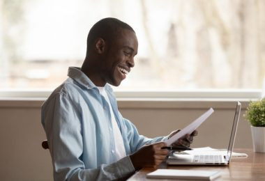 African guy sitting at table reading college acceptance letter with good news