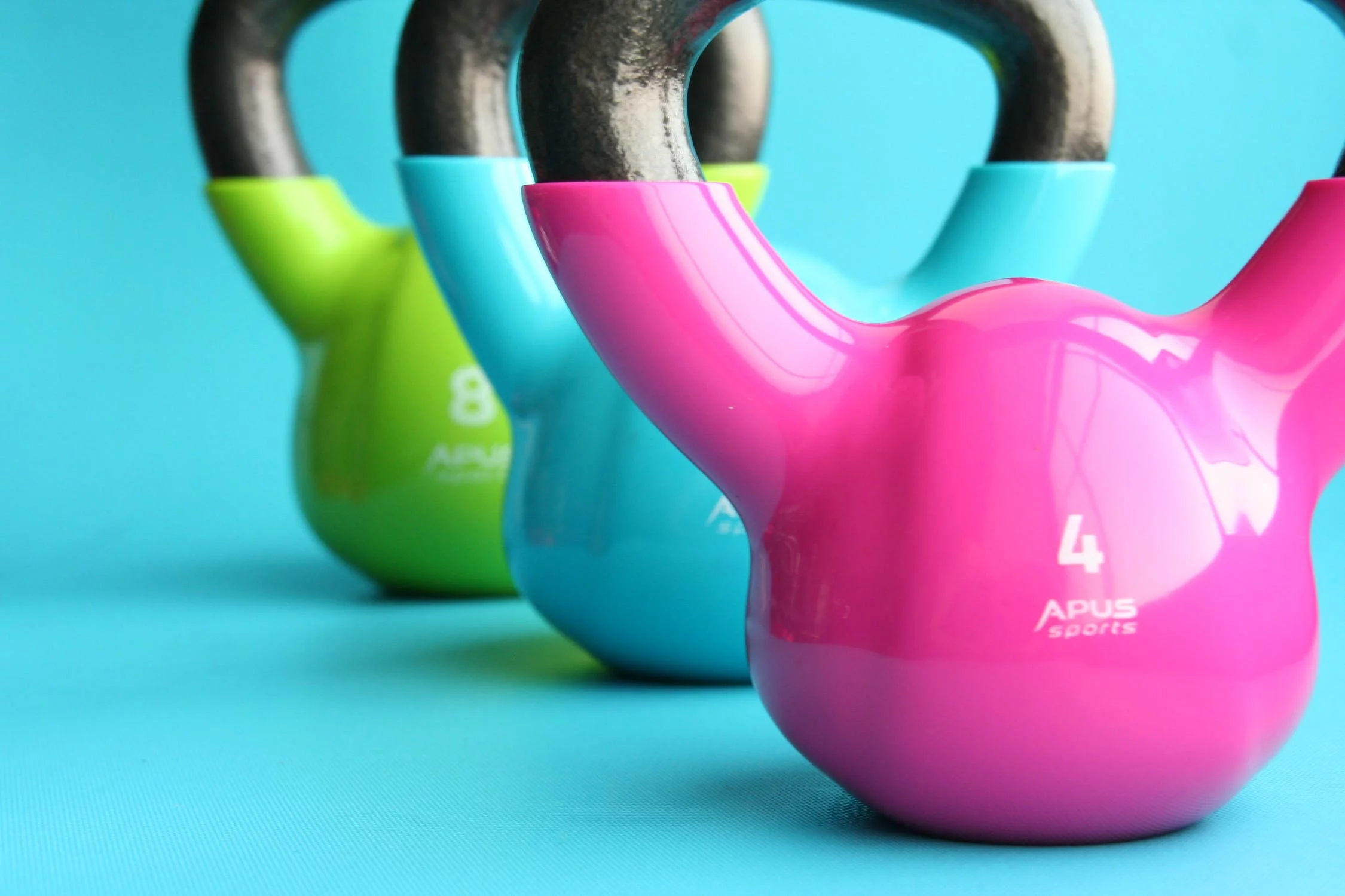pink, blue and green kettlebells on blue background