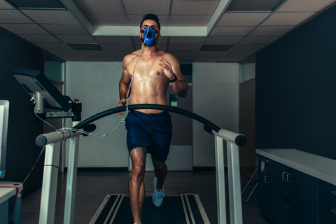 Athelte running on treadmill in shorts with face mask on