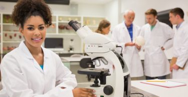 female college student smiling in lab coat sitting next to microscope