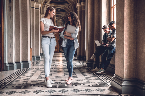 two female college students standing in hallway holding books while talking to each other
