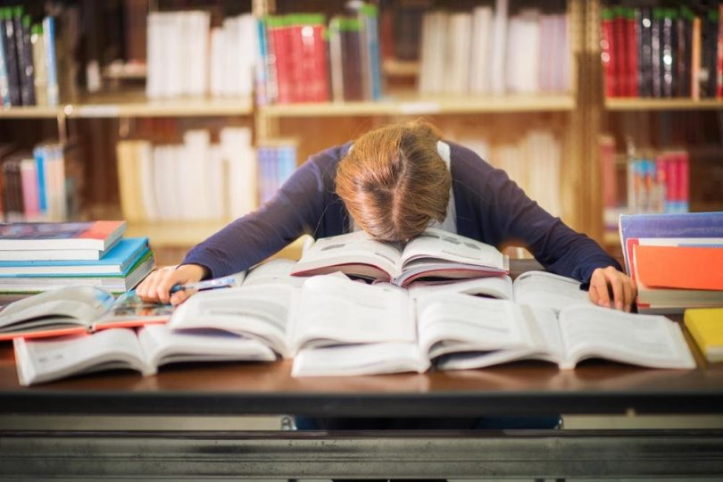 College student laying head on pile of text books on desk