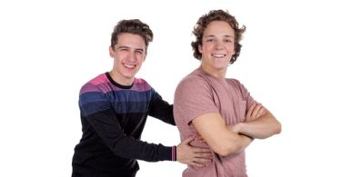 two male college roommates smiling on white background