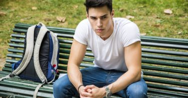 male student sitting on bench after being rejected by college admissions