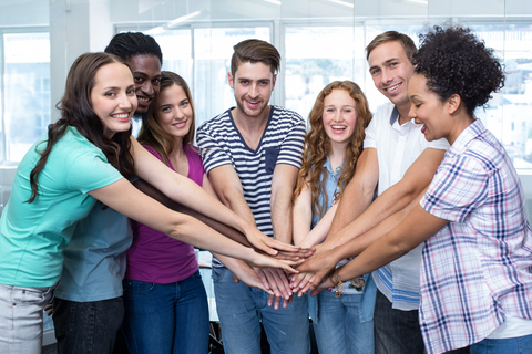 group of smiling college students all putting their hands in the middle of a circle