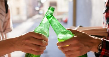 college students holding beer bottles while tapping them together