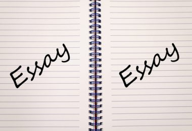 open coiled lined notebook with the words essay on both sides