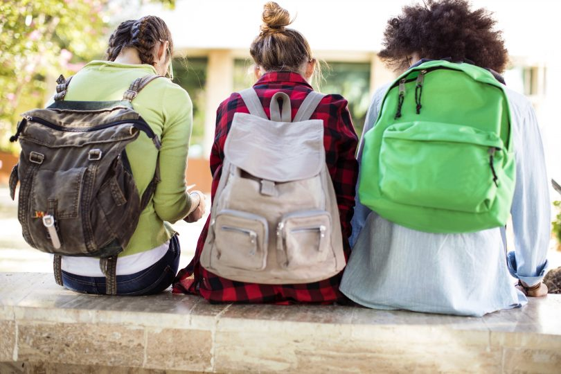 three female college students wearing backpacks while sitting on steps