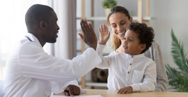 african american pediatrician giving a high five to a little boy patient