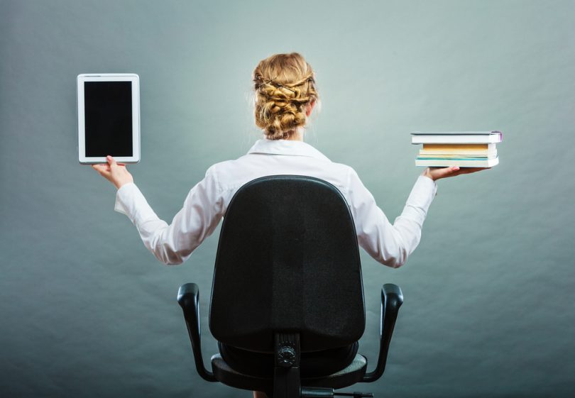 woman sitting in chair holding books in right hand and tablet in the left hand