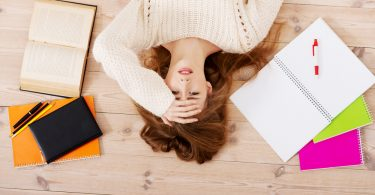 stressed student laying on floor with study materials